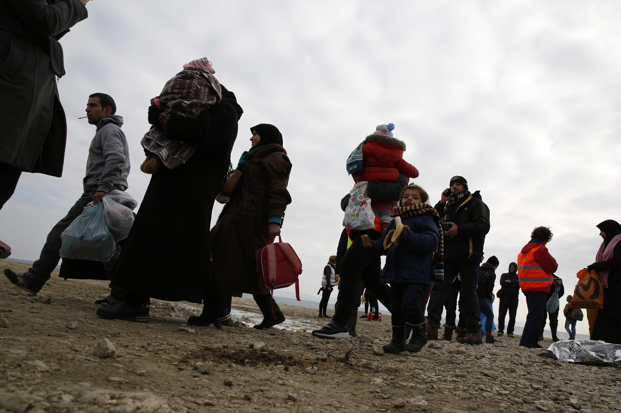 Migrants and refugees walk to a waiting bus after arriving on a rubber dinghy on a beach on the Greek island of Lesbos, January 29, 2016. Photo: Darrin Zammit Lupi